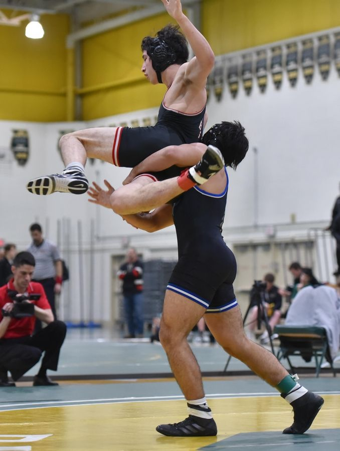 Barrington's Kai Conway is thrown by Highland Park's Pano Dosos in their 160-pound championship bout at the Stevenson High School wrestling regional meet in Lincolnshire Saturday.
