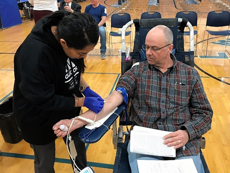 Jocelyn Morin. phlebotomist at blood service provider Vitalant, draws blood from Arlington Heights resident Rich DeMuro at Sunday's blood drive at Our Lady of the Wayside School in Arlington Heights.