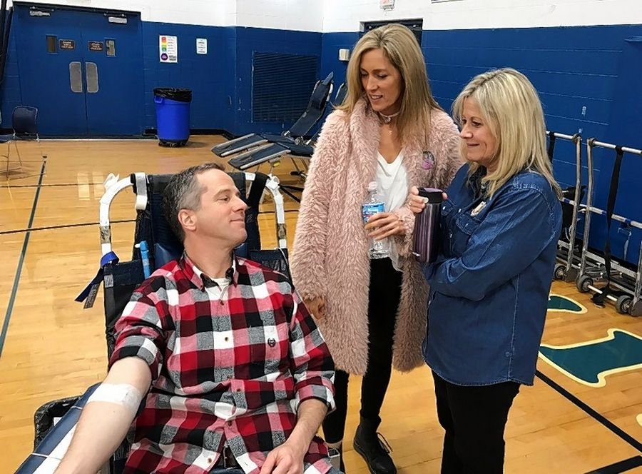 Sisters Robin Holum, center, and Beth Chamberlain chat with their brother, Joe Ramicone, as he gives blood in honor of his late niece, Emily Holum.