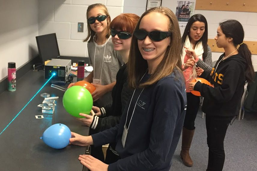 Attendees at CLC's 2019 STEM for Girls event participate in a laser-light demonstration.