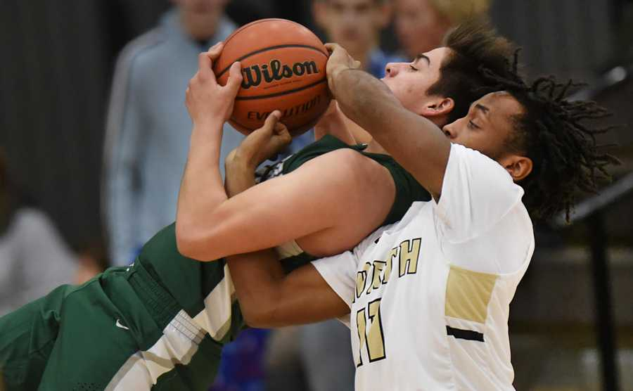 Graylake North's Tony Hines reaches around Grayslake Central's Daniel Rogers to force a jump ball at North High School Tuesday.