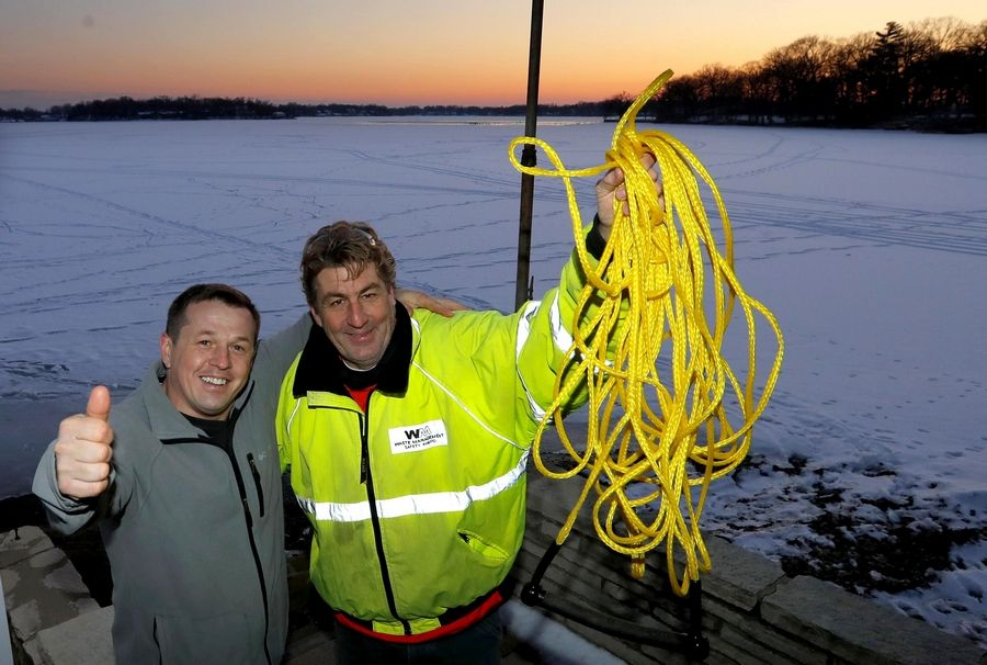Sean Mors, right, rescued Sebastian Chadzynski, left, on Sunday after Chadzynski fell through the ice on Lake Catherine near Antioch. Sean raises the rope Tuesday that he had used to snag Sebastian. Mors' footprints from the rescue can still be seen running near the shoreline behind them.
