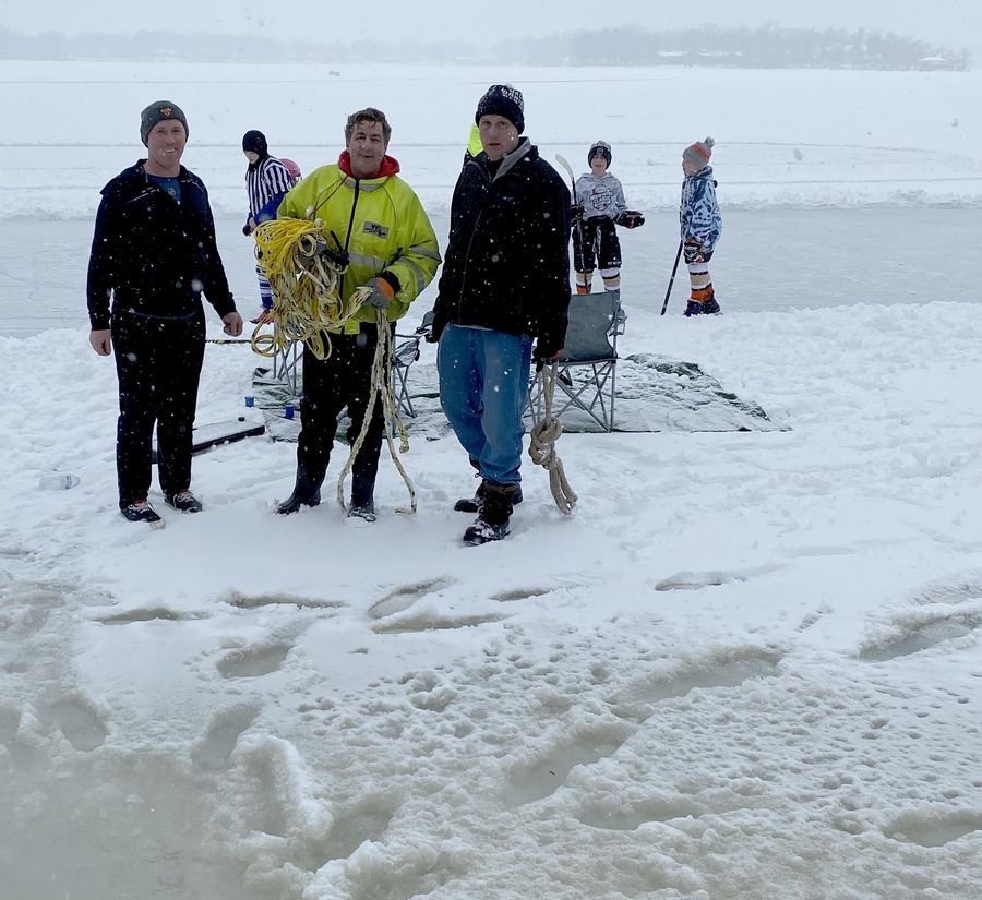 Sean Mors, center, rescued Sebastian Chadzynski Sunday after Chadzynski fell through the ice on Lake Catherine near Antioch. Jake Norwood, left, and Chris Little, right, helped with the rescue.