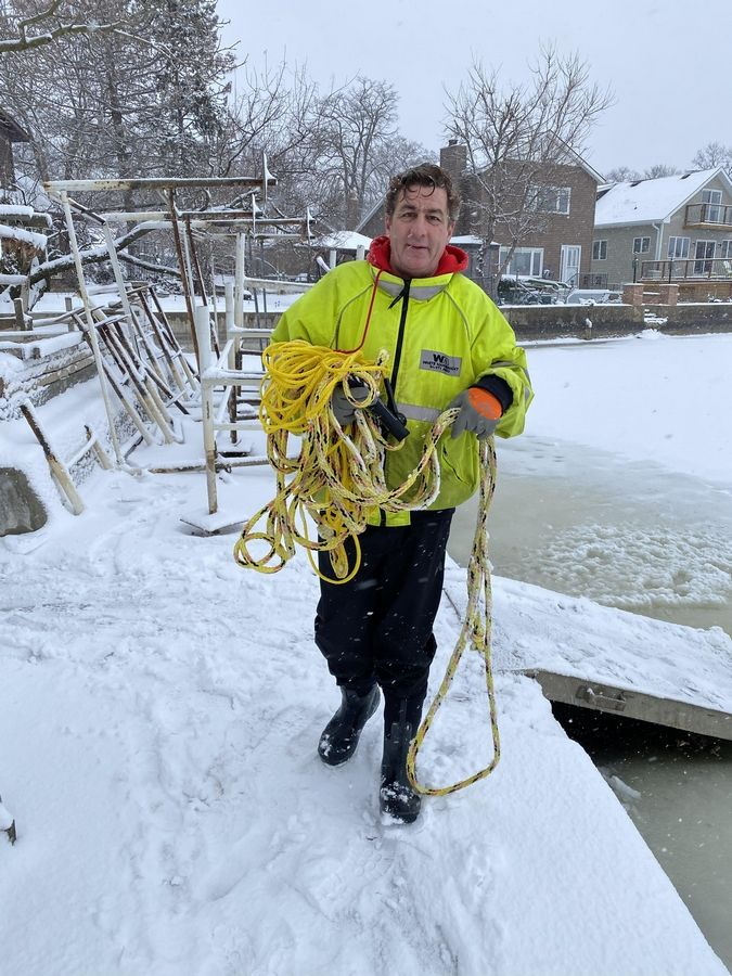 Sean Mors carries the rope he used to rescue rescued Sebastian Chadzynski after Chadzynski into the icy waters of Lake Catherine near Antioch on Sunday.