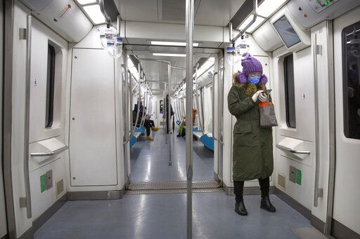 A woman wears safety goggles, a face mask, and rubber gloves as she rides a nearly empty subway train in Beijing, Friday, Feb. 14, 2020. China on Friday reported another sharp rise in the number of people infected with a new virus, as the death toll neared 1,400.