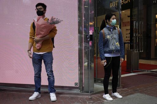 A man wearing protective face mask waits at a street corner with a bouquet on Valentine's Day in Hong Kong, Friday, Feb. 14, 2020. China on Friday reported another sharp rise in the number of people infected with a new virus, as the death toll neared 1,400.