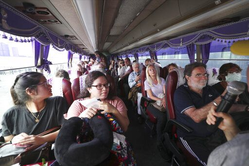 Passengers of the MS Westerdam sit in a busa after they disembarked from the cruise ship, owned by Holland America Line, at the port of Sihanoukville, Cambodia, Friday, Feb. 14, 2020. Hundreds of cruise ship passengers long stranded at sea by virus fears cheered as they finally disembarked Friday and were welcomed to Cambodia.