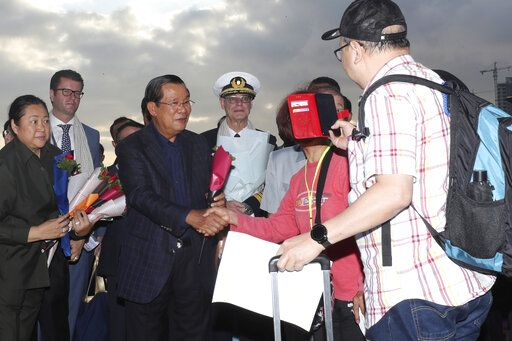 Cambodia's Prime Minister Hun Sen, center left, greets passengers after they disembarked from the MS Westerdam, owned by Holland America Line, at the port of Sihanoukville, Cambodia, Friday, Feb. 14, 2020. Hundreds of cruise ship passengers long stranded at sea by virus fears cheered as they finally disembarked Friday and were welcomed to Cambodia.