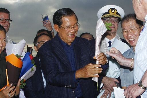 Cambodia's Prime Minister Hun Sen, center, gives a flower to a passenger who disembarked from the MS Westerdam, owned by Holland America Line, at the port of Sihanoukville, Cambodia, Friday, Feb. 14, 2020. Hundreds of cruise ship passengers long stranded at sea by virus fears cheered as they finally disembarked Friday and were welcomed to Cambodia.