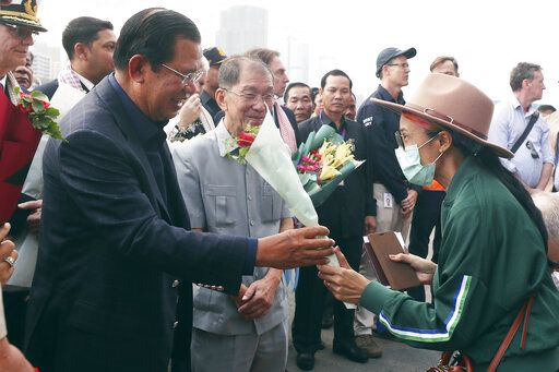 Cambodia's Prime Minister Hun Sen, left, gives a bouquet of flowers to a passenger who disembarked from the MS Westerdam, owned by Holland America Line, at the port of Sihanoukville, Cambodia, Friday, Feb. 14, 2020. Hundreds of cruise ship passengers long stranded at sea by virus fears cheered as they finally disembarked Friday and were welcomed to Cambodia.