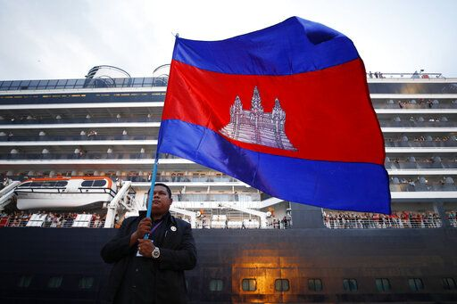 A Cambodian man holds his national flag in front of the MS Westerdam, owned by Holland America Line, dockked at the port of Sihanoukville, Cambodia, Friday, Feb. 14, 2020. Hundreds of cruise ship passengers long stranded at sea by virus fears cheered as they finally disembarked Friday and were welcomed to Cambodia.