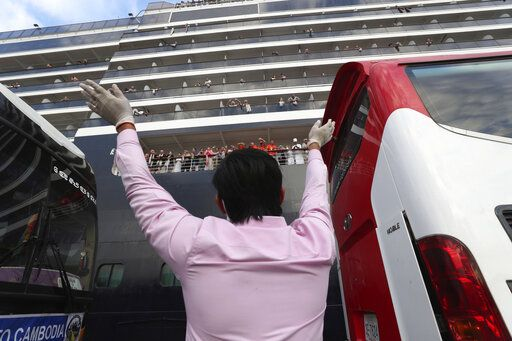 A man waves to passengers of the MS Westerdam, owned by Holland America Line, docked at the port of Sihanoukville, Cambodia, Friday, Feb. 14, 2020. Hundreds of cruise ship passengers long stranded at sea by virus fears cheered as they finally disembarked Friday and were welcomed to Cambodia.