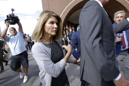 FILE - In this Aug. 27, 2019, file photo, actress Lori Loughlin departs federal court in Boston, after a hearing in a nationwide college admissions bribery scandal. A new prosecution filing in the college admissions cheating case targets defense claims by Loughlin and her fashion designer husband Mossimo Giannulli. The Los Angeles Times reports the filing Tuesday, Jan.14, 2020, includes hundreds of pages of emails, transcripts of recorded calls and financial and academic records.