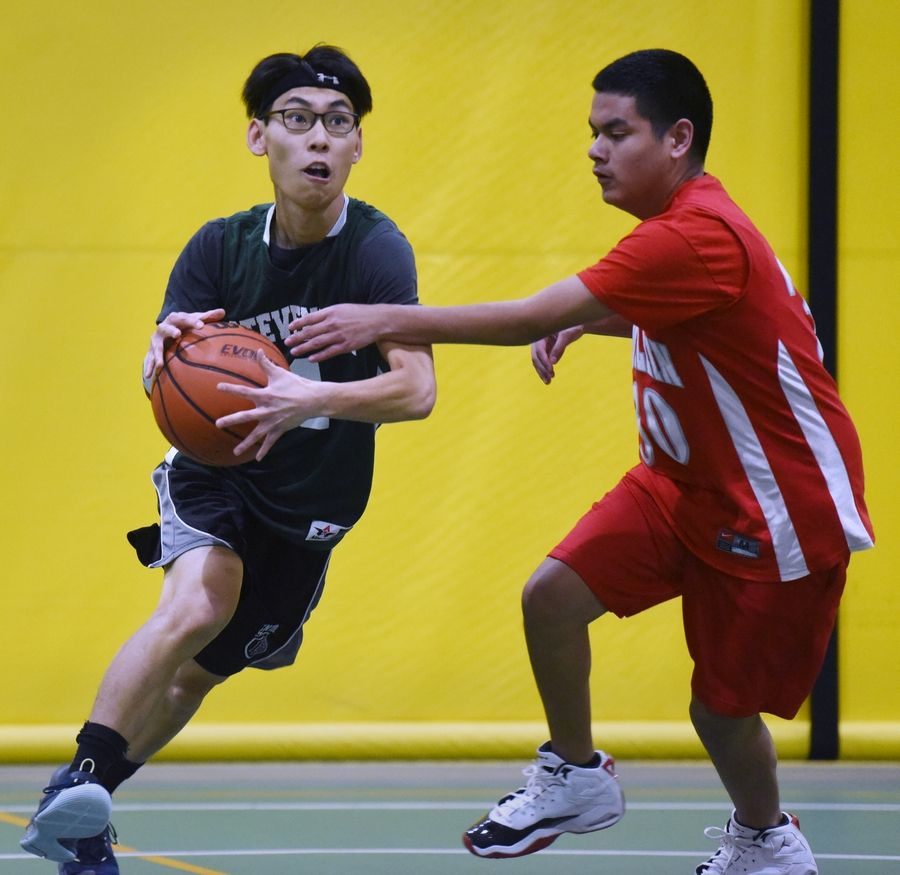 Allied basketball player David Ha, on the left, is supervised by Isaias Hernandez of the Mundelein Mustangs during a Special Olympics game at Stevenson High School in Lincolnshire.