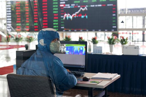 A worker wearing a protective suit reacts in front of an infrared temperature machine in the lobby of the Shanghai Stock Exchange building in Shanghai, China, Friday, Feb. 14, 2020. Asian shares mostly fell Friday as investors turned cautious following a surge in cases of a new virus in China that threatens to crimp economic growth and hurt businesses worldwide.