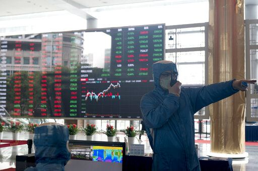 A worker wearing a protective suit gestures in front of an infrared temperature machine in the lobby of the Shanghai Stock Exchange building in Shanghai, China, Friday, Feb. 14, 2020. Asian shares mostly fell Friday as investors turned cautious following a surge in cases of a new virus in China that threatens to crimp economic growth and hurt businesses worldwide.