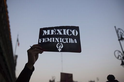 "A demonstrator holds up a stencil of the Spanish message: ""Mexico Femicide"" in Mexico City, Friday, Feb. 14, 2020. The demonstration against gender violence comes after last week's vicious murder of Ingrid Escamilla by her husband and controversy unleashed by the leaking of images of her body to the press, in a country where an average of 10 women are killed every day."