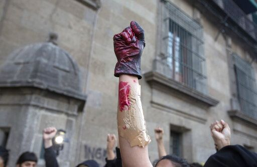A woman holds up her fist covered in fake blood during a protest against gender violence outside the National Palace, the presidential office and residence, in Mexico City, Friday, Feb. 14, 2020. The demonstration comes after the murder of Ingrid Escamilla by her husband and controversy unleashed by the leaking of images of her body to the press, in a country where an average of 10 women are killed every day.