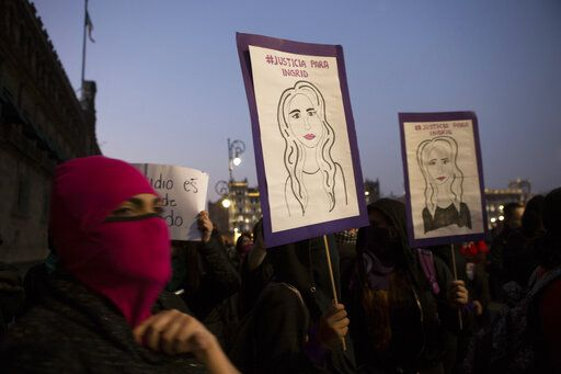 Masked, female protesters hold drawings resembling Ingrid Escamilla, who was killed by her husband last week, during a protest against gender violence outside the National Palace, the presidential office and residence, in Mexico City, Friday, Feb. 14, 2020. The demonstration against gender violence comes after Escamilla's vicious murder and controversy unleashed by the leaking of images of her body to the press, in a country where an average of 10 women are killed every day.