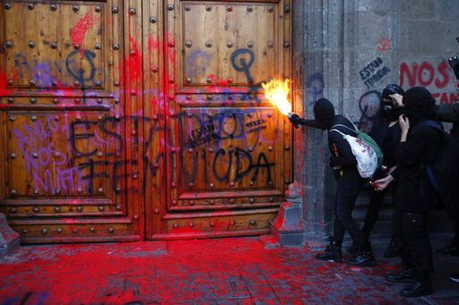 "A masked, female protester sprays fire at the entrance to the National Palace, the presidential office and residence, after demonstrators covered it in fake blood and the Spanish message: ""Femicide State,"" in Mexico City, Friday, Feb. 14, 2020. The demonstration against gender violence comes after last week's vicious murder of Ingrid Escamilla by her husband and controversy unleashed by the leaking of images of her body to the press, in a country where an average of 10 women are killed every day."