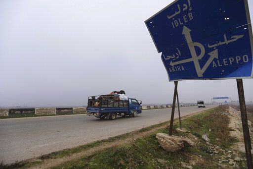 FILE - This Monday, Dec. 23, 2019, file photo, civilians ride in a truck as they flee Maaret al-Numan, Syria, ahead of a government offensive. The M5 highway, recaptured by President Bashar Assad's forces this week, is arguably the most coveted prize in Syria's civil war. The strategic highway is vital for Syria's  economy as well as for moving troops.