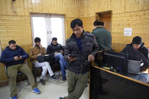 In this Jan. 30, 2020, photo, Kashmiri journalists browse the internet on their mobile phones inside the media center set up by government authorities in Srinagar, Indian controlled Kashmir. Six months after India stripped restive Kashmir of its semi-autonomy, enforcing a total communications blackout, it has restored limited internet at slow speeds with access only to government-approved websites. Since Modi came into power in 2014, the internet has been suspended more than 365 times in India, according to the global digital rights group Access Now.