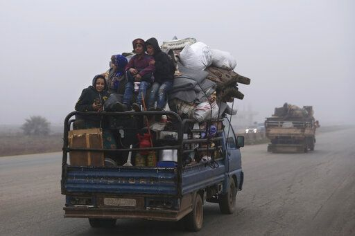 FILE - This Dec. 23, 2019, file photo, civilians ride in a truck as they flee Maaret al-Numan, Syria, ahead of a government offensive. The M5 highway, recaptured by President Bashar Assad's forces, is arguably the most coveted prize in Syria's civil war. The strategic highway is vital for Syria's  economy as well as for moving troops.