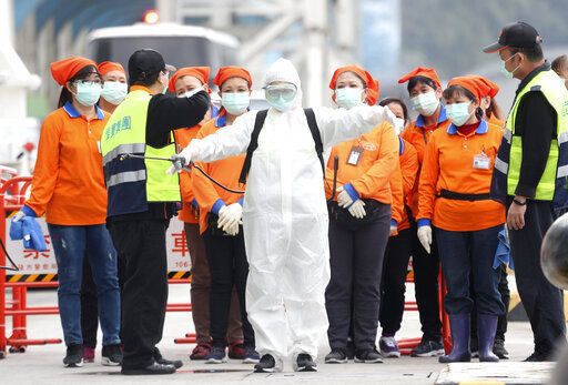 FILE - In this Saturday, Feb, 8, 2020, file photo, an epidemic prevention worker in a protective suit stands by to get on board the cruise ship SuperStar Aquarius which was denied right to dock by Japan over fears of spread of virus and returned to dock at Keelung port in New Taipei City, Taiwan. Taiwan's exclusion from the World Health Organization is pitting health concerns against geopolitics during the current crisis over a new virus. Taiwan has called repeatedly for it to be allowed to participate in WHO, from which it has been barred by China. So strong is China's diplomatic pressure that Taiwan can no longer take part in the organization's annual World Health Assembly, even as an observer.
