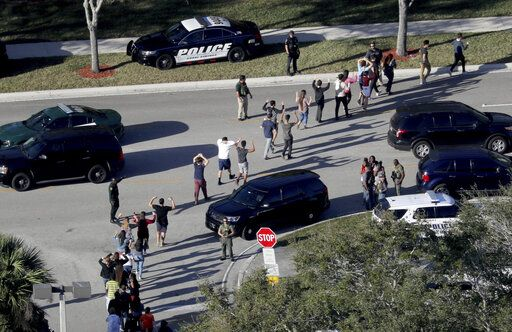 FILE - In this Wednesday, Feb. 14, 2018, file photo, students hold their hands in the air as they are evacuated by police from Marjory Stoneman Douglas High School in Parkland, Fla., after a shooter opened fire on the campus. A Florida law that allows judges to bar anyone deemed dangerous from possessing firearms has been used 3,500 times since its enactment after the 2018 high school massacre. An Associated Press analysis shows the law is being used unevenly around the state. (Mike Stocker/South Florida Sun-Sentinel via AP, File)