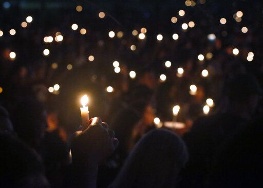 FILE - In this Thursday, Feb. 15, 2018, file photo, attendees hold up their candles at a candlelight vigil for the victims of the shooting at Marjory Stoneman Douglas High School, in Parkland, Fla. A Florida law that allows judges to bar anyone deemed dangerous from possessing firearms has been used 3,500 times since its enactment after the 2018 high school massacre. An Associated Press analysis shows the law is being used unevenly around the state.