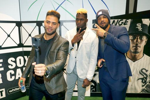 Chicago White Sox's Yoan Moncada, left, Luis Robert, center, and Jose Abreu pose for a video during the team's annual fan convention Friday, Jan. 24, 2020, in Chicago.