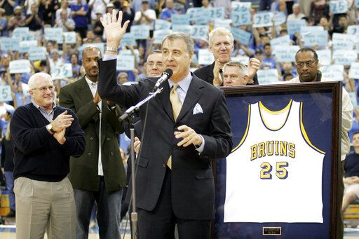 FILE - In this Dec. 18, 2004, file photo, former UCLA basketball player Gail Goodrich, foreground, waves to the crowd during a ceremony retiring his UCLA No. 25 jersey at half time of the UCLA-Michigan game in Los Angeles. More than three decades after the 1988 NBA All-Star weekend in Chicago, some details of the classic slam dunk contest showdown between Michael Jordan and Dominique Wilkins are a bit fuzzy to Hall of Famer Gail Goodrich. One of five judges for the competition, the former Los Angeles Lakers' great is, however, certain of a few things: His Airness soared to a slightly higher level than the Human Highlight Reel, there was no pressure to crown Jordan the slam dunk king on his home court and the judges were not in cahoots.