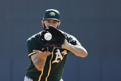 Oakland Athletics' Mike Fiers runs a drill during spring training baseball practice, Thursday, Feb. 13, 2020, in Mesa, Ariz.