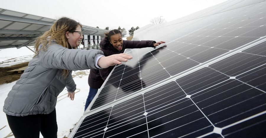 Big Hollow Middle School students Noelle Patrick, 13, of Ingleside and Meghan Klipstein, 13, of Lakemoor give the solar panels they helped bring to the district a ceremonial hug.