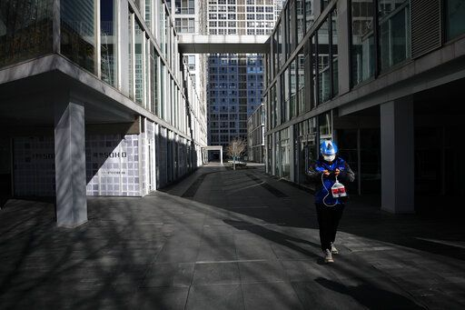A food delivery worker passes a deserted compound of a commercial office building during the lunch break in Beijing, Monday, Feb. 17, 2020. Chinese authorities on Monday reported a slight upturn in new virus cases and hundred more deaths, as the military dispatched hundreds more medical workers and extra supplies to the city hit hardest by the 2-month-old outbreak.