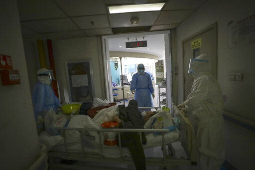 In this Sunday, Feb. 16, 2020, photo, medical workers transfer a new coronavirus patient at a hospital in Wuhan in central China's Hubei province. Chinese authorities on Monday reported a slight upturn in new virus cases and hundred more deaths for a total of thousands since the outbreak began two months ago. (Chinatopix via AP)