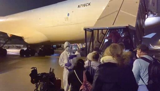 In this image from a video taken on Monday, Feb. 17, 2020, U.S. passengers who evacuated off the quarantined cruise ship the Diamond Princess,  board a Kalitta Air plane bound for the U.S., at Haneda airport in Tokyo.(Cheryl and Paul Molesky via AP)