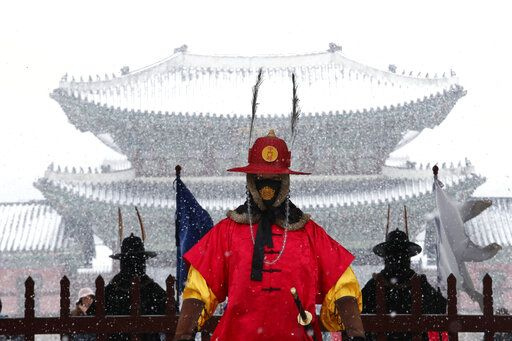 An Imperial guard wearing a face mask stands in the snow outside the Gyeongbok Palace, the main royal palace during the Joseon Dynasty in Seoul, South Korea, Monday, Feb. 17, 2020. Chinese authorities on Monday reported a slight upturn in new virus cases and hundred more deaths for a total of thousands since the outbreak began two months ago.