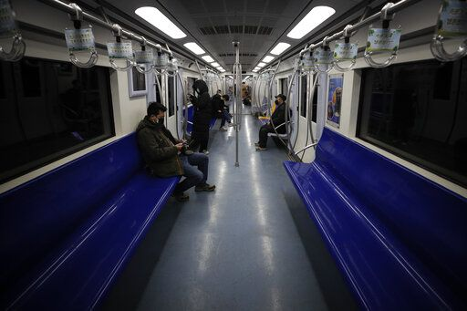 Commuters ride in a quiet subway train during the morning rush hour in Beijing, Monday, Feb. 17, 2020. Chinese authorities on Monday reported a slight upturn in new virus cases and hundred more deaths for a total of thousands since the outbreak began two months ago.