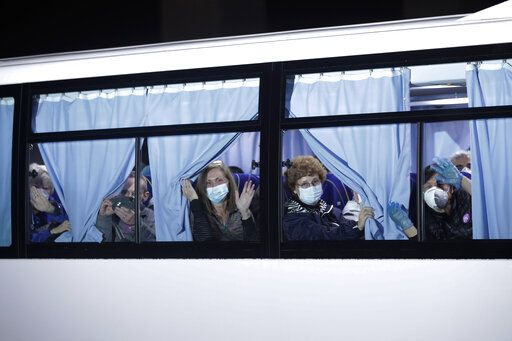 Buses carrying passengers from the quarantined Diamond Princess cruise ship leave a port in Yokohama, near Tokyo, Monday, Feb. 17, 2020. A group of Americans are cutting short a 14-day quarantine on the Diamond Princess cruise ship in the port of Yokohama, near Tokyo, to be whisked back to America. But they will have to spend another quarantine period at a U.S. military facility to make sure they don't have the new virus that's been sweeping across Asia.