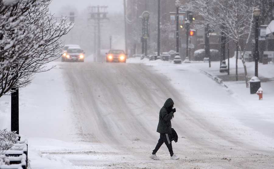 A pedestrian crosses Highland Avenue in downtown Elgin as snow continues to fall Thursday morning.