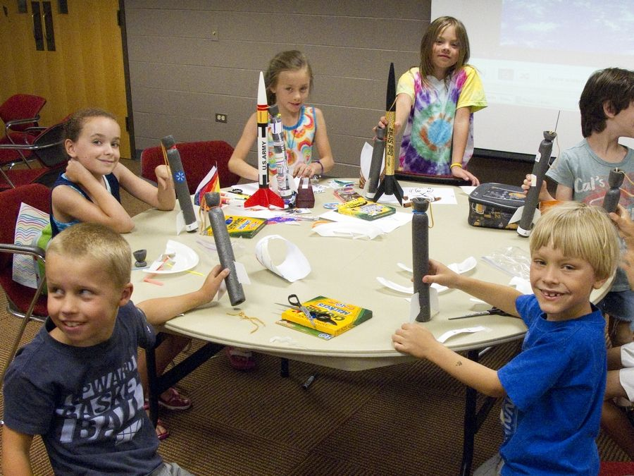 Children in a previous summer Explore camp at the College of Lake County assemble model rockets.College of Lake County