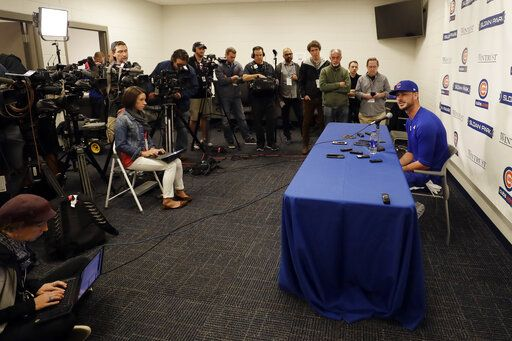 Chicago Cubs third baseman Kris Bryant, right, speaks to reporters during spring training baseball Saturday, Feb. 15, 2020, in Mesa, Ariz.