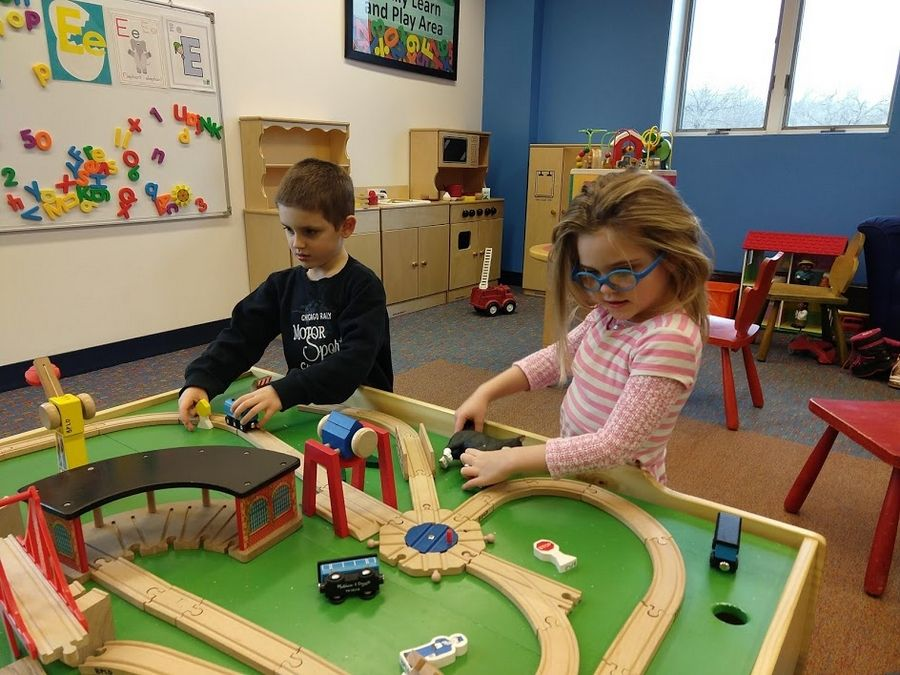 Marie (5) and George (5) Kasten enjoy playing with the various toys available at the Bartlett Public Library District.