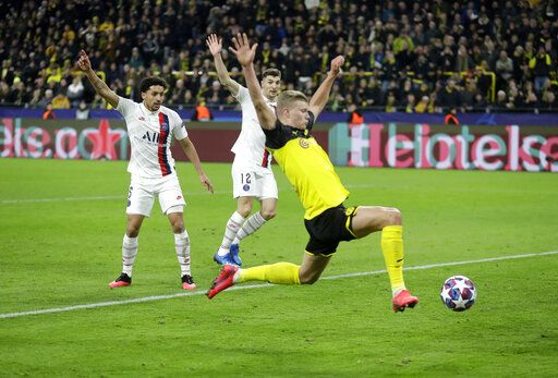 Dortmund's Erling Braut Haaland, front, scores his side's opening goal during the Champions League round of 16 first leg soccer match between Borussia Dortmund and Paris Saint Germain in Dortmund, Germany, Tuesday, Feb. 18, 2020.