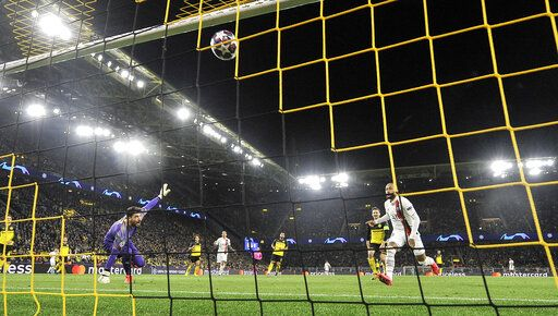 PSG's Neymar, right, scores against Dortmund's goalkeeper Roman Buerki during the Champions League round of 16 first leg soccer match between Borussia Dortmund and Paris Saint Germain in Dortmund, Germany, Tuesday, Feb. 18, 2020.