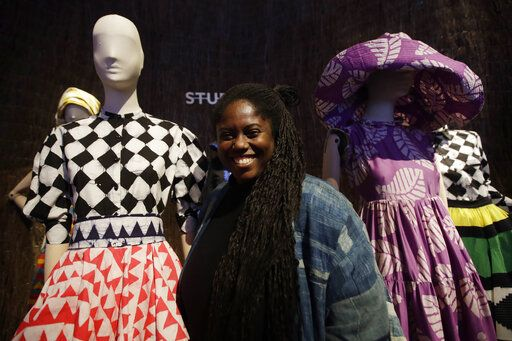 Fashion designer Abrima Erwia smiles as she poses with creations part of the Studio 189 women's Fall-Winter 2020-2021 collection, that was presented in Milan, Italy, Wednesday, Feb. 19, 2020. Italy's Chamber of fashion dedicate at a space at a fashion hub, to a selection of young African brands belonging to a new generation of designers embodying the powerful identity of African fashion.