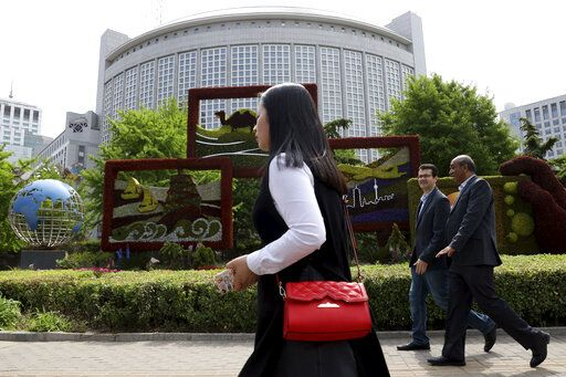 In this April 19, 2019, photo, foreigners pass by the Chinese Foreign Ministry in Beijing, China. China on Wednesday, Feb. 19, 2020 said it has revoked the press credentials of three reporters for the U.S. newspaper Wall Street Journal over a headline for an opinion column deemed by the government to be racist and slanderous.