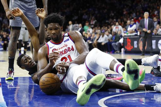 Philadelphia 76ers' Joel Embiid, center, battle for a loose ball with Brooklyn Nets' Caris LeVert during overtime in an NBA basketball game, Thursday, Feb. 20, 2020, in Philadelphia. Philadelphia won 112-104.