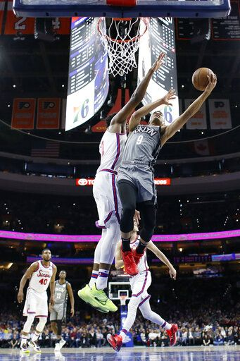 Brooklyn Nets' Timothe Luwawu-Cabarrot (9) goes up for a shot past Philadelphia 76ers' Joel Embiid (21) during the first half of an NBA basketball game, Thursday, Feb. 20, 2020, in Philadelphia.